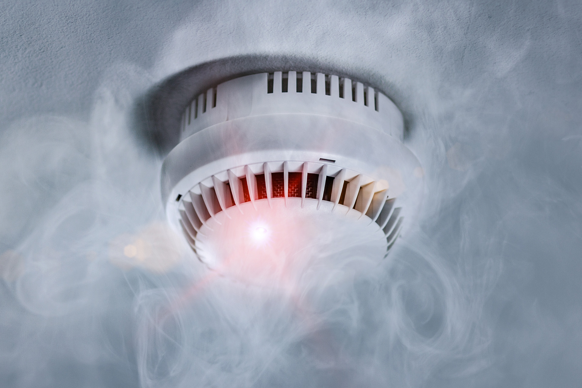 Smoke detector on ceiling surrounded by smoke